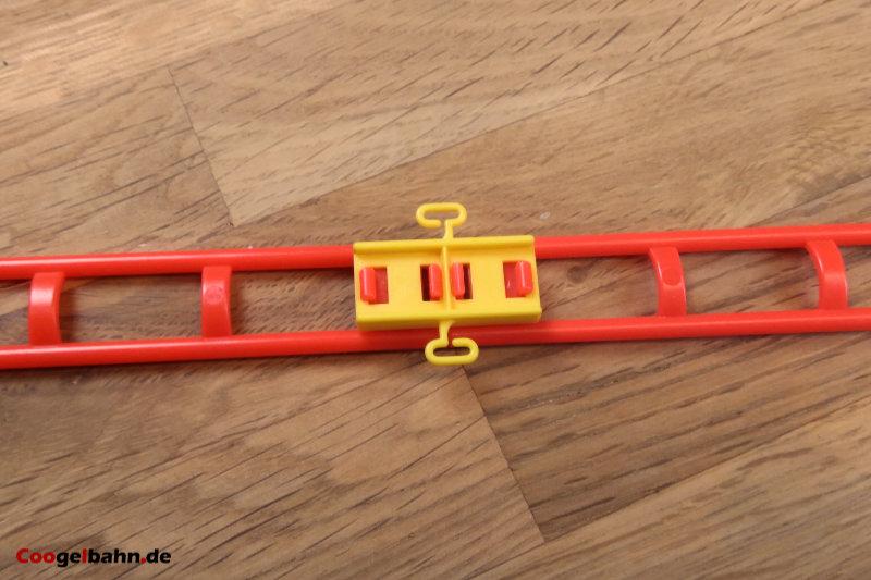 Der gelbe Clip dient als Verbinder für die Schienen
